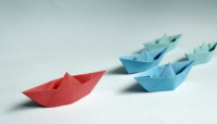 Blue paper boats led by a red paper boat.
