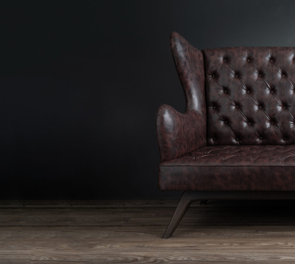 dark brown leather couch against grey wall